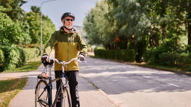 Iäkäs mies taluttaa pyörää tien laidassa