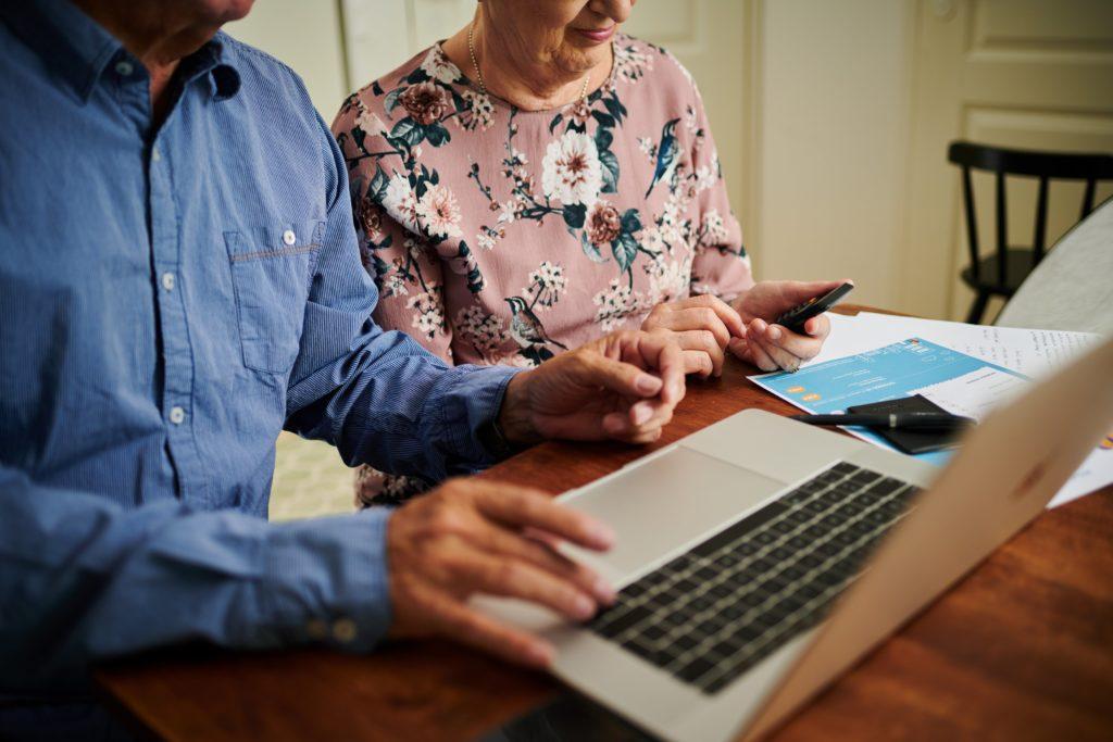Vanhempi pariskunta tietokoneen ääressä