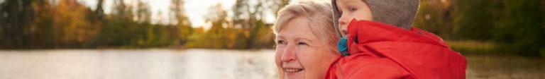 Luonto antaa voimaa - iäkäs nainen katselee syksyistä järvimaisemaa pieni lapsi sylissä