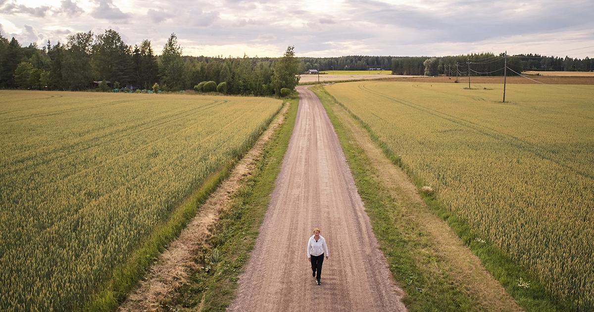 Nainen kävelee hiekkatiellä vihertävien viljapeltojen välissä. kohti vanhuutta. Kuntavaalit 2021 teemakuva.