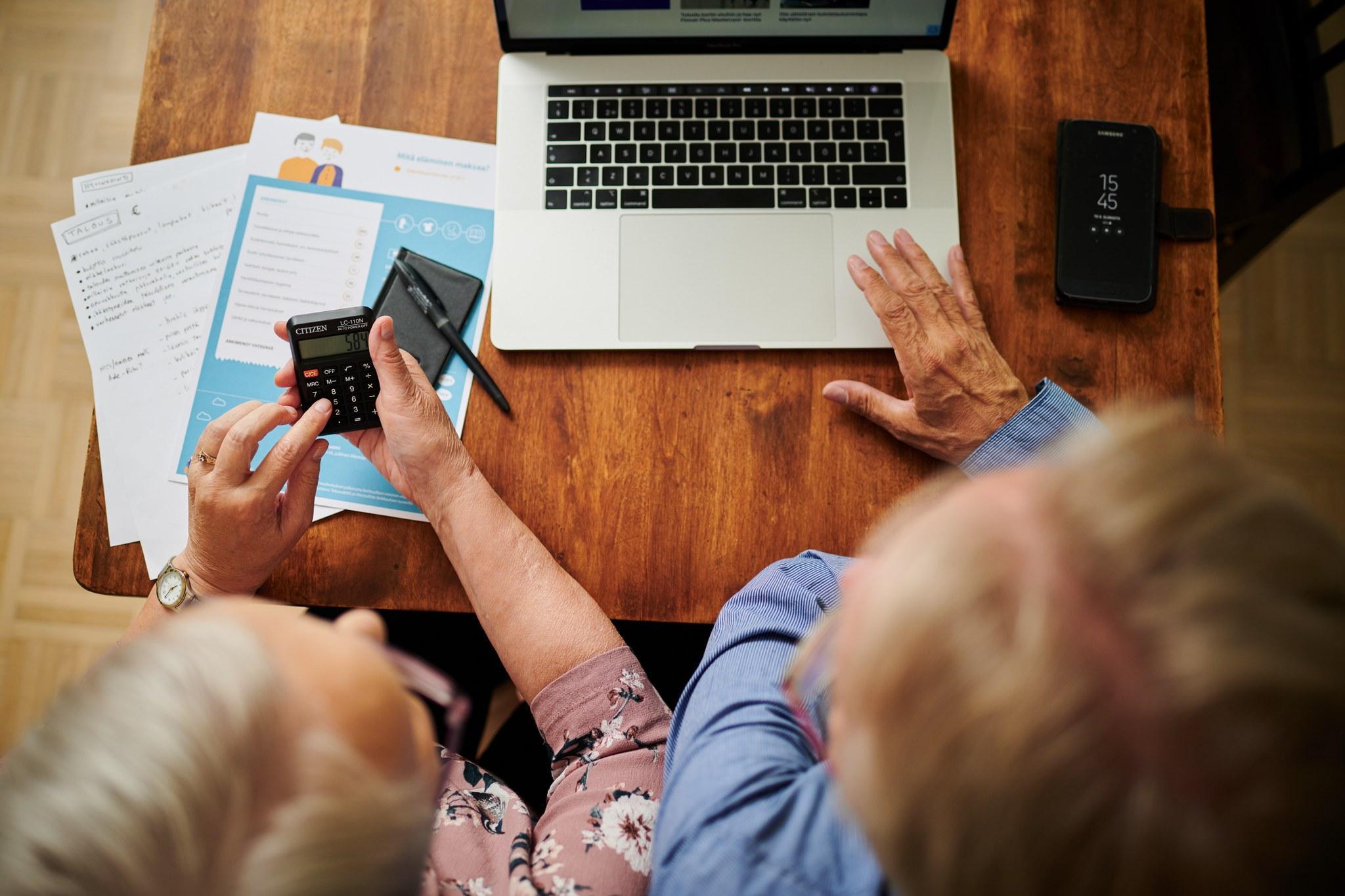 Iäkäs pariskunta hoitamassa asioita tietokoneen äärellä