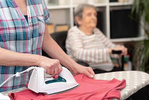 Perhehoitaja silittää vaatteita ja vanhus nuokkuu taustalla.