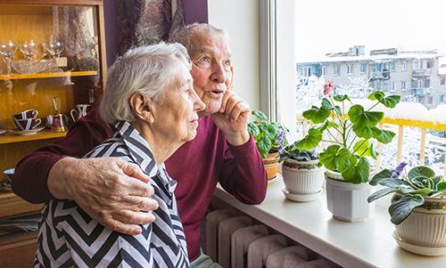 Vanha pariskunta katsoo ulos asuntonsa ikkunasta.