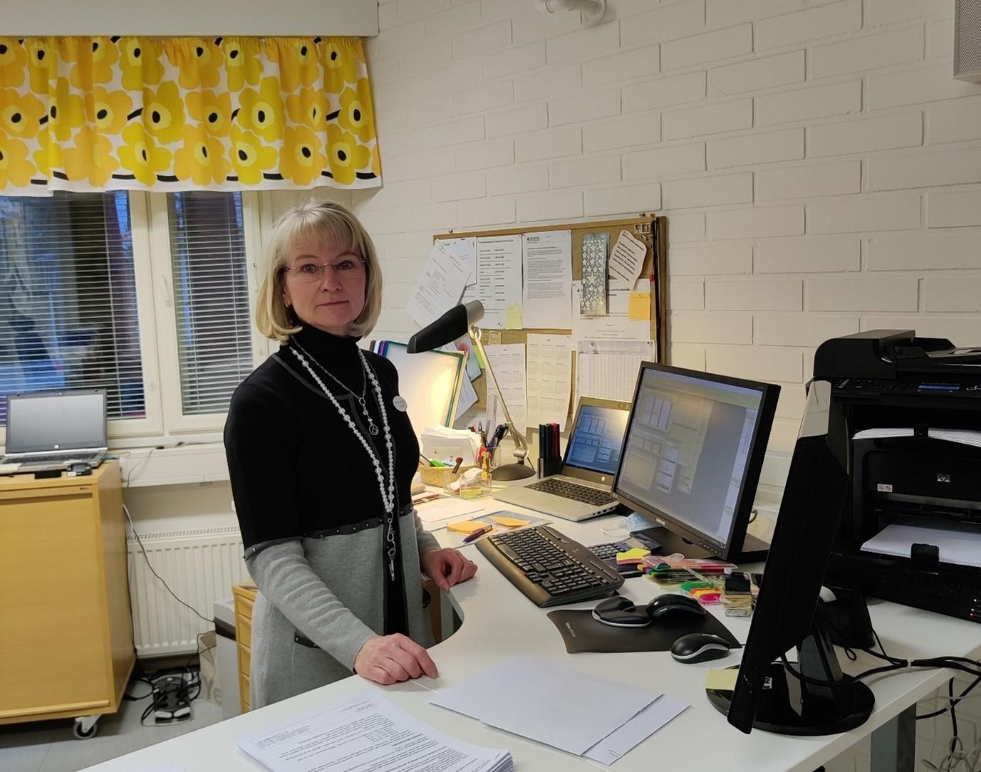 Toiminnanjohtaja Tiina Marjava työpöydän äärellä.