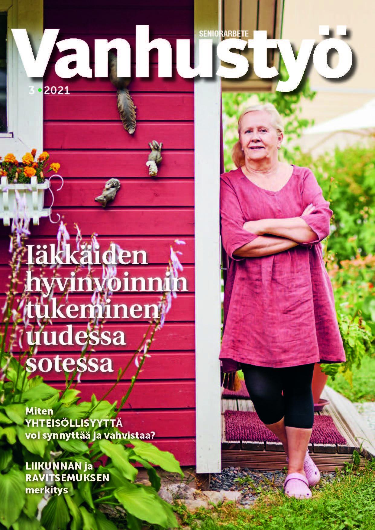 Vanhempi nainen seisoo puutarhassa ja nojaa punaiseen mökkiin.