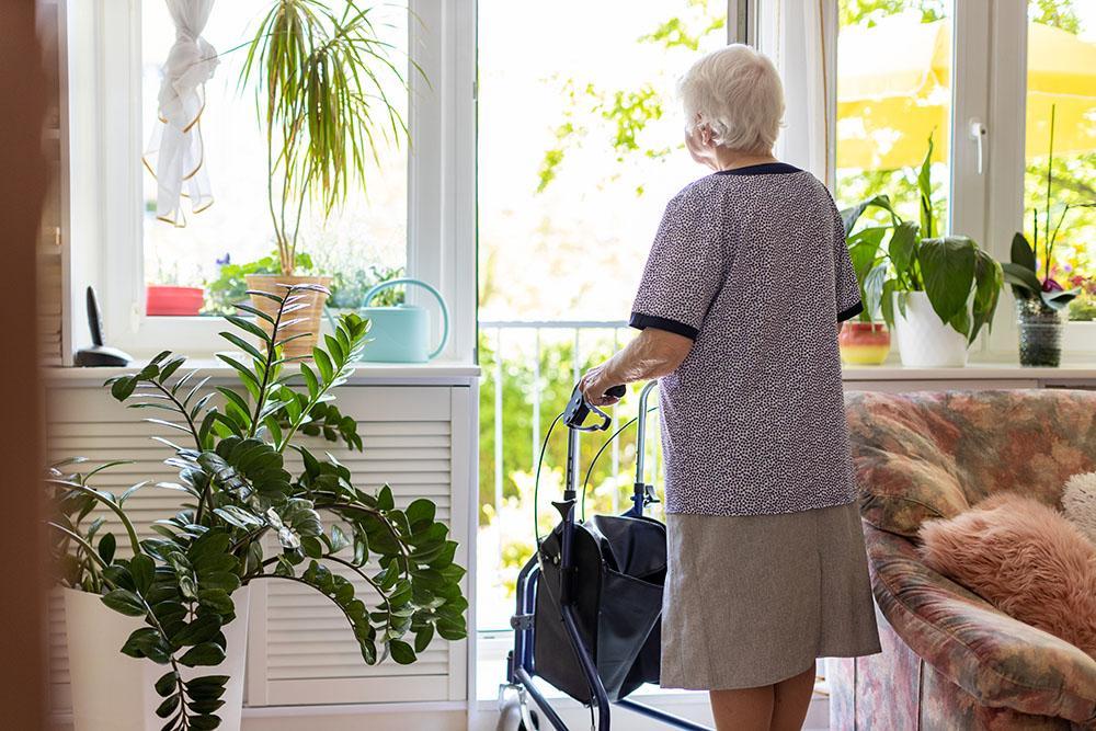 Vanha nainen seisoo rollaattorin kanssa ja atsoo ulos ikkunasta.