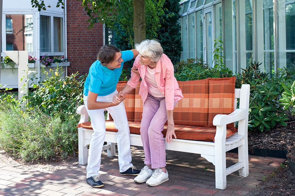 Hoitaja auttaa vanhaa naista ylös pihapenkiltä.