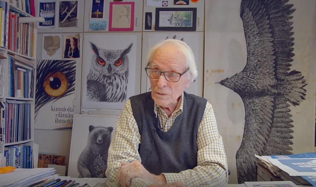 Graafikko Erik Bruun istuu työpöytänsä äärellä ja taustalla kuvia piirroksista.