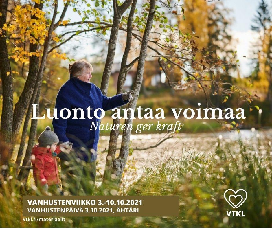 Vanhempi nainen pienen lapsen kanssa syksyisessä maisemassa järven rannalla.