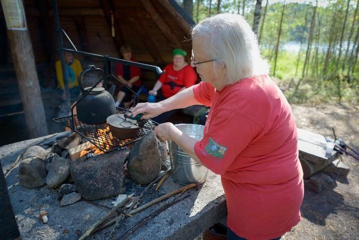 Iäkkäitä ihmisiä istumassa laavulla. Vanha nainen keittää nokikahvia.