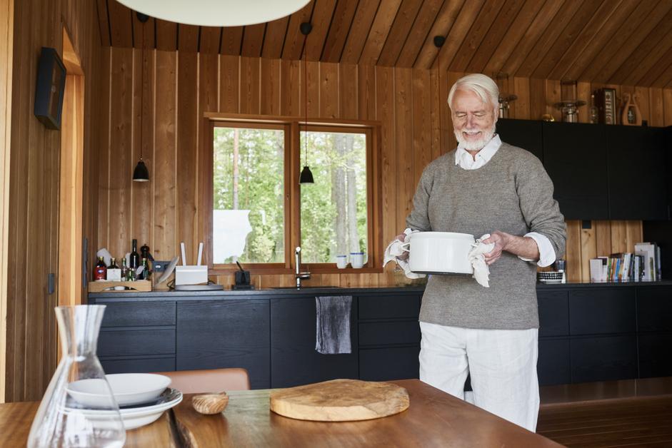 Iäkäs mies kantaa kattilaa ruokapöytään