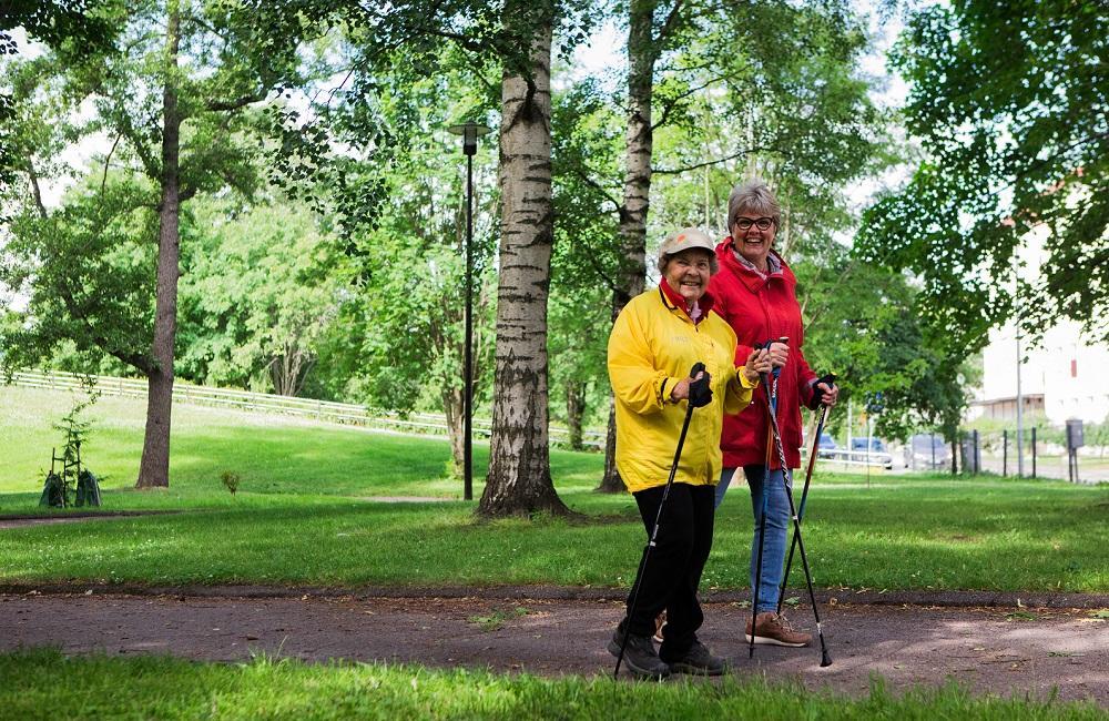 Kaksi iäkästä naista sauvakävelyllä kesäisessä puistossa